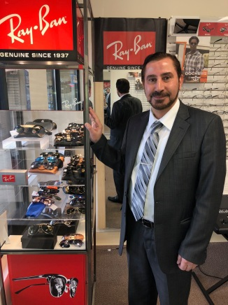 Dr. Salim Rufo Auraha stands near a Ray Ban display within his store.